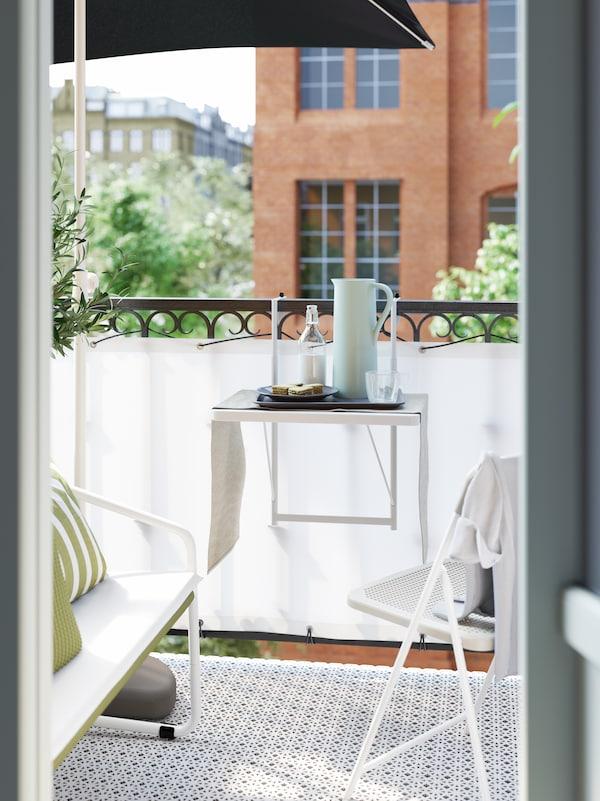 Ein kleiner weisser Balkontisch an einem Balkongeländer. Darauf stehen eine Karaffe, ein Teller mit Essen und Getränke.
