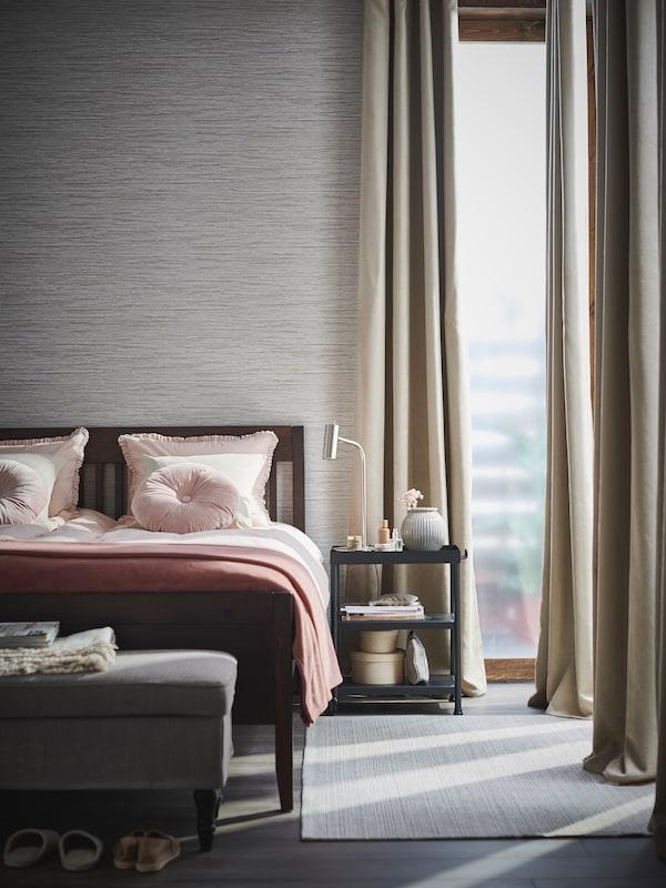 Une fenêtre ornée de rideaux opaques BRITNA et un lit IDANÄS muni d'ensembles housses de couette KRANSKRAGE dans une chambre claire et ordonnée.