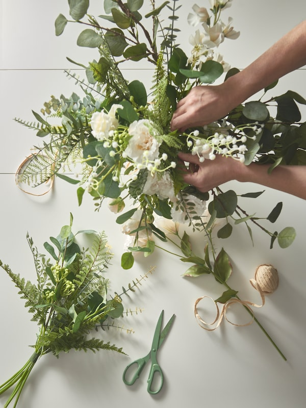 A display of artificial flowers being worked on by a pair of hands, with scissors and ribbon used to make a bouquet.