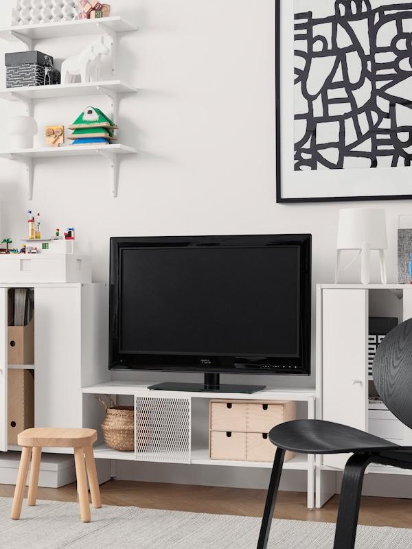 Et hvidt tv-bord, et sort tv, et indrammet sort-hvidt print, hvide skabe med låger og pyntegenstande.