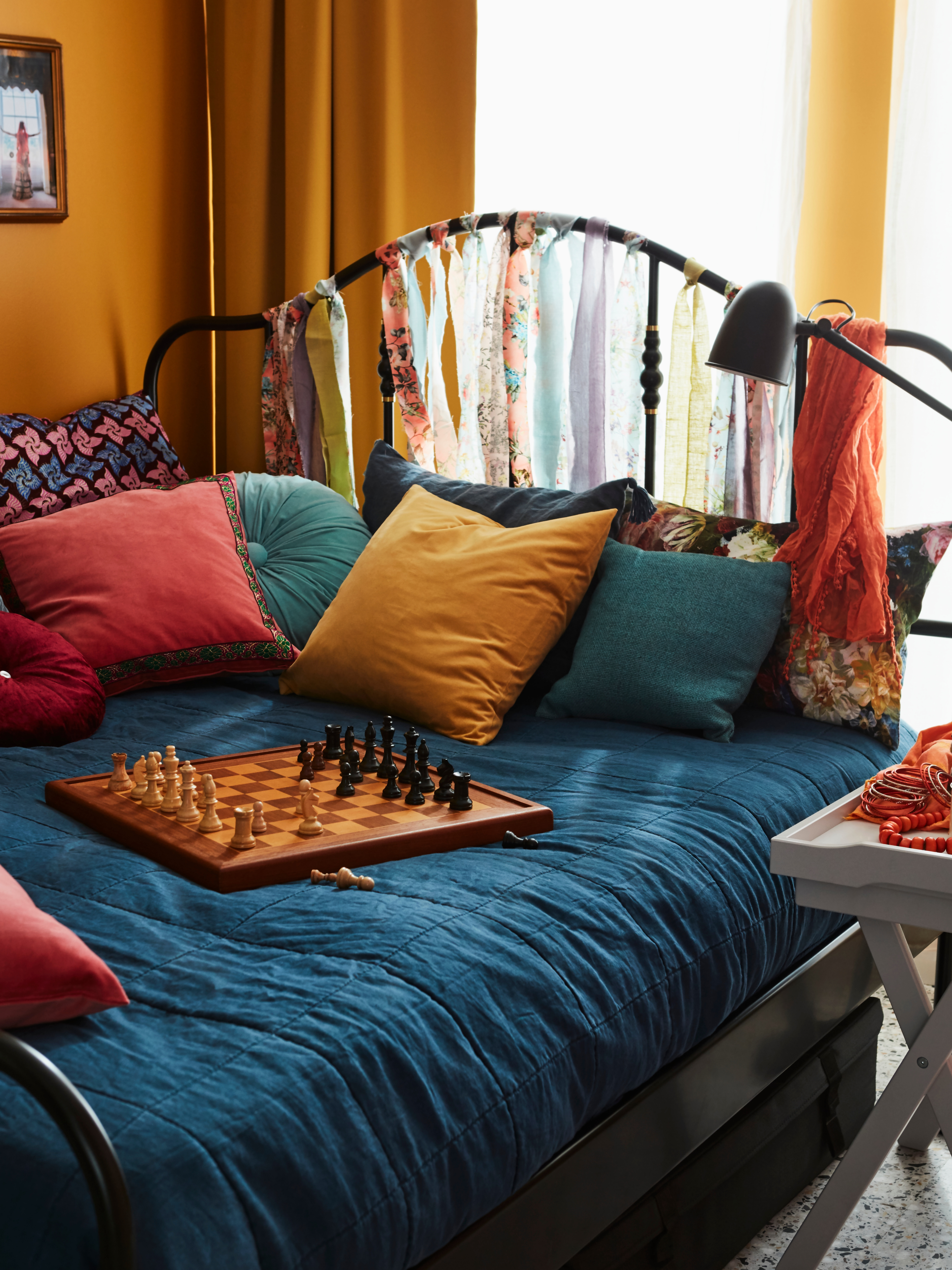 A colourfully made bed is used like a sofa with cushions and a chess game on top of a black-coated steel SAGSTUA bed frame.