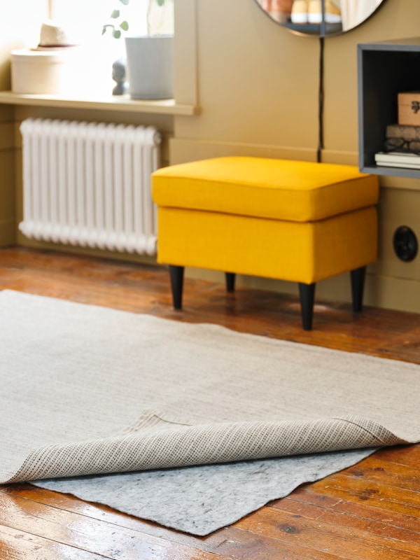 A rug on a wooden floor rolled back to show the underlay, with a yellow footstool behind, a radiator and storage unit.