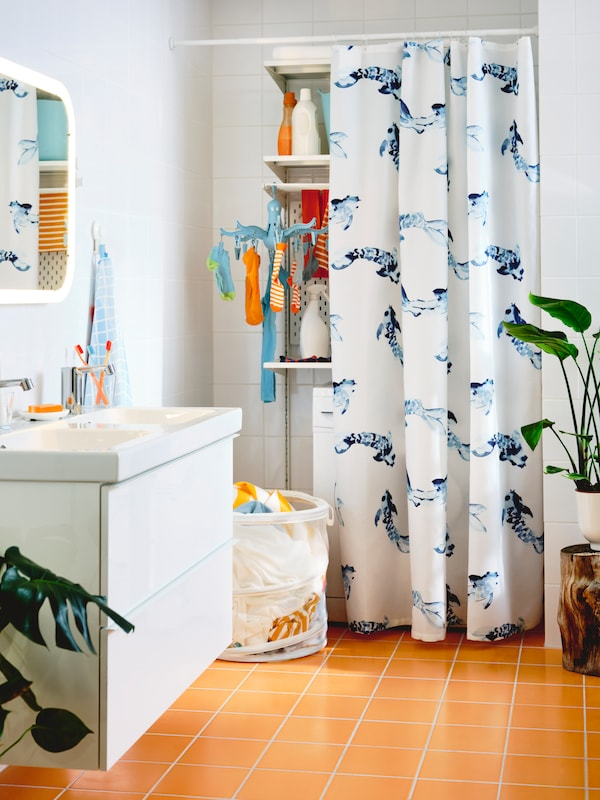 A bathroom with a white GODMORGON wash-stand with two drawers, an ODENSVIK washbasin and a half-hidden laundry area.