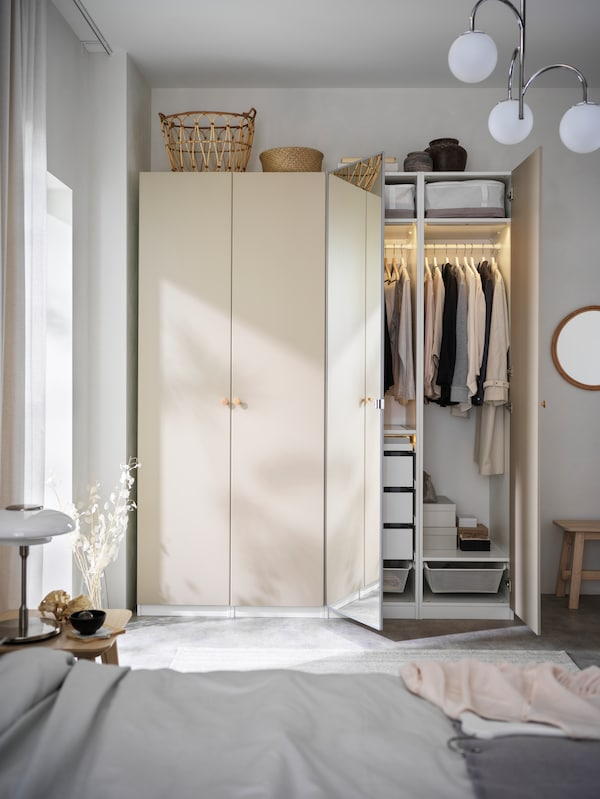 A PAX/REINSVOLL wardrobe with doors open against a white wall.
