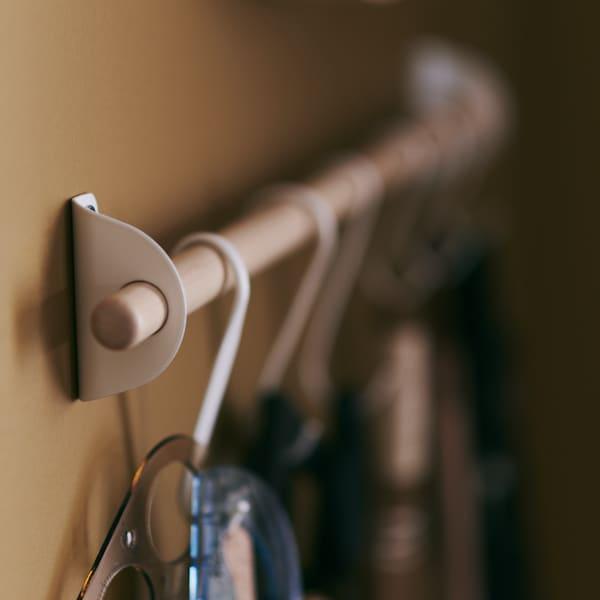 صورة عن قرب لسكة تعليق NEREBY، مصنوعة من خشب البتولا، تتدلى منها خطافات NEREBY بيضاء.