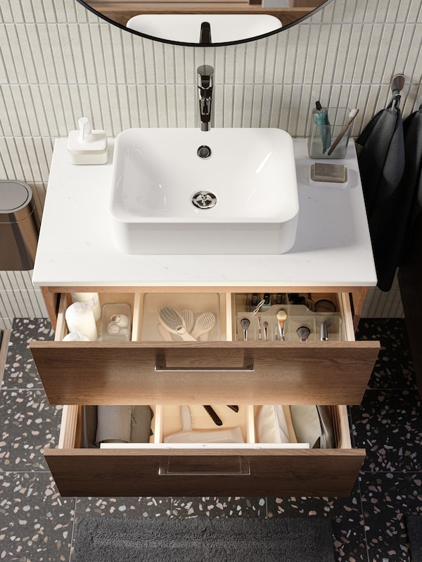 A white bathroom with a white sink cabinet with 2 drawers below a white mirror with shelf next to a white high cabinet.