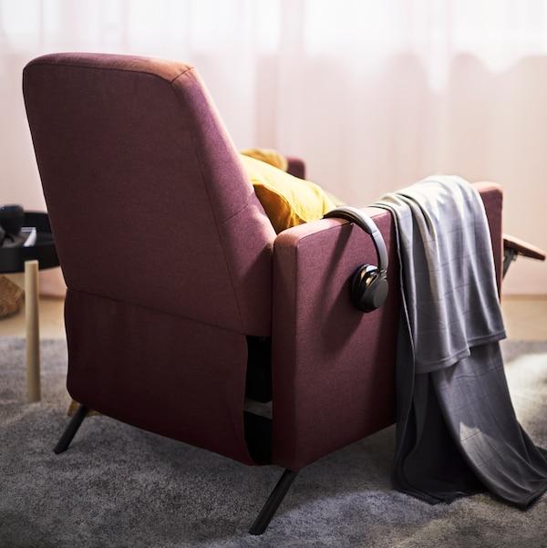 Un fauteuil confort rouge foncé GISTAD face à une fenêtre, un coussin jaune sur l'assise.