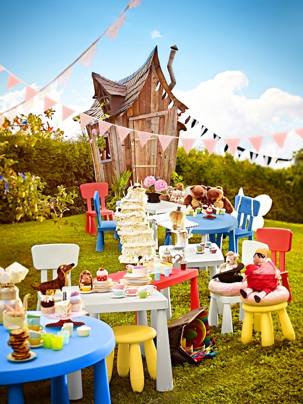 MAMMUT tables, stools and chairs with plates, food and soft toys on top stand outside on a lawn near a wooden house.