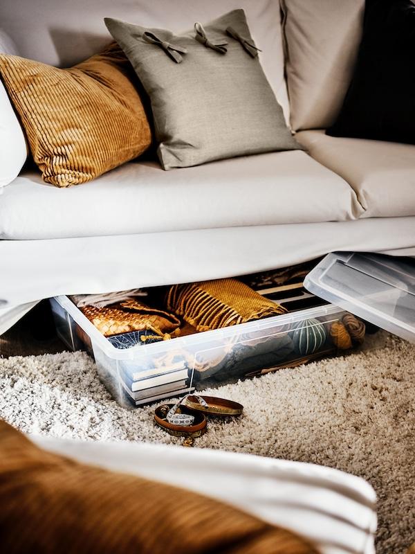 Une grande boîte SAMLA transparente et étroite contenant des livres et des textiles. Elle se trouve sur un tapis clair à poils longs sous un canapé BACKSÄLEN.