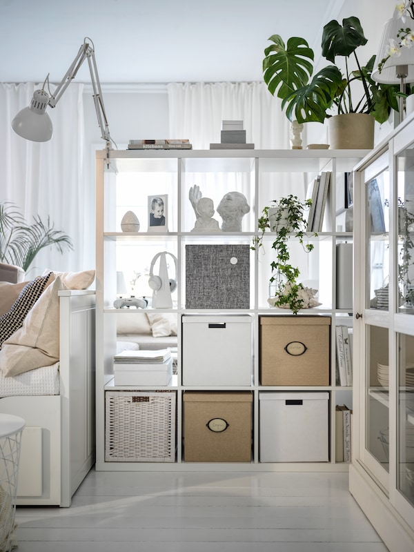 A living room with a room-dividing, white KALLAX shelving unit and a white HEMNES day-bed beside it.