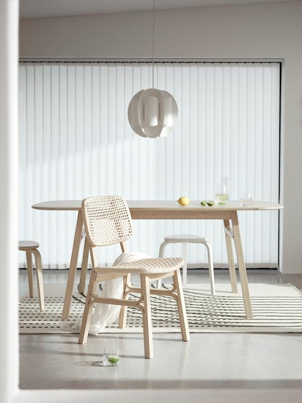 Ljus matplats som är minimalt möblerad med VOXLÖV stol i bambu, VOXLÖV matbord samt två pallar.