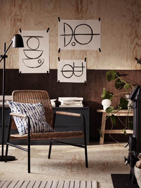 A lamp next to a rattan armchair with a cushion on top in a room with painted pictures taped to a wooden wall.