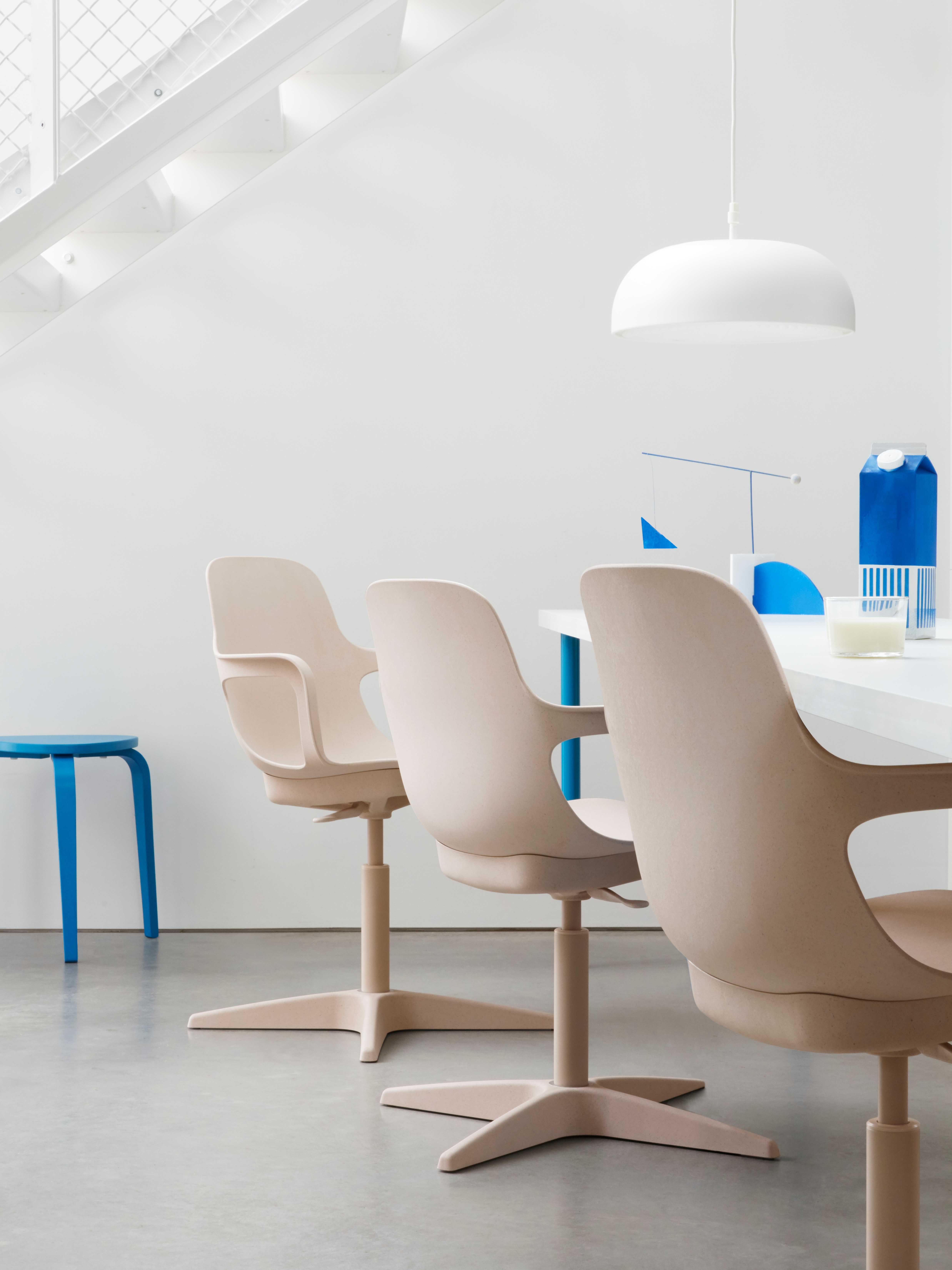 Three beige swivel ODGER chairs next to a long white table with a white pendant lamp and a blue stool.