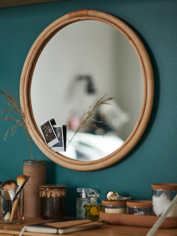 A round mirror on a green wall, above a shelf with diverse items like jars, brushes and a notebook placed on it.