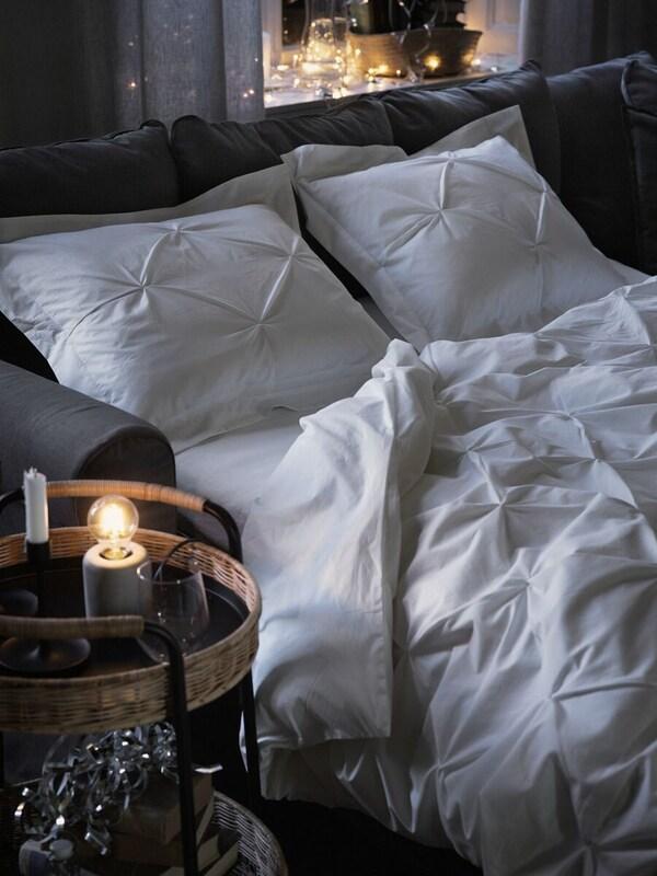 Een donkergrijze slaapbank 's avonds opgemaakt met TRUBBTÅG beddengoed. Bij het bed staat een ronde LUBBAN roltafel met opbergruimte.