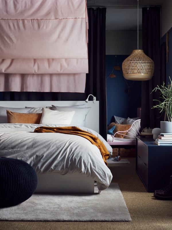 โคมไฟแขวนเพดานไม่ไผ่ MISTERHULT/มิสเตร์ฮุลท์ แขวนอยู่ใกล้กับเตียง MALM/มาล์ม สีขาวที่ตั้งอยู่หน้าฉากกั้นห้องซึ่งทำด้วยผ้าม่าน