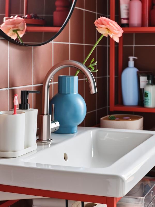 Lavabo branco con dispensador de xabón, soporte para cepillo de dentes e bandexa de cor branca, e floreiro azul cunha flor rosa.