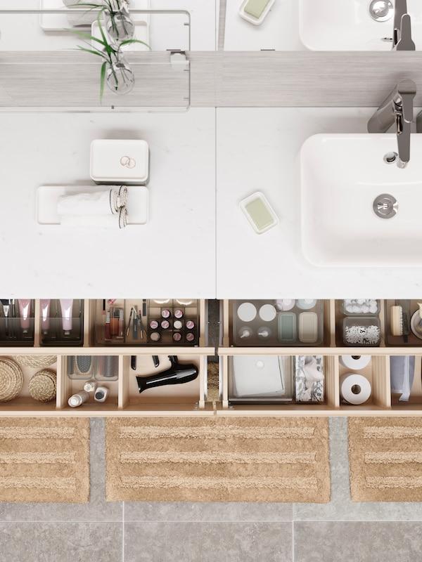 Sink berwarna putih dengan kotak dan tuala yang digulung, dua laci terbuka yang terdapat kotak GODMORGON yang disusun secara kemas.
