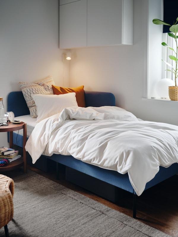 Sengestel polstret med mellemblå KNISA tekstil med en hjørnegavl, et hvidt sengesæt og puder.