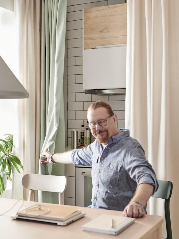 Un home que utiliza a súa cociña como oficina pecha unhas cortinas MOALINA verdes e brancas para ocultar o mesado e os fogóns.