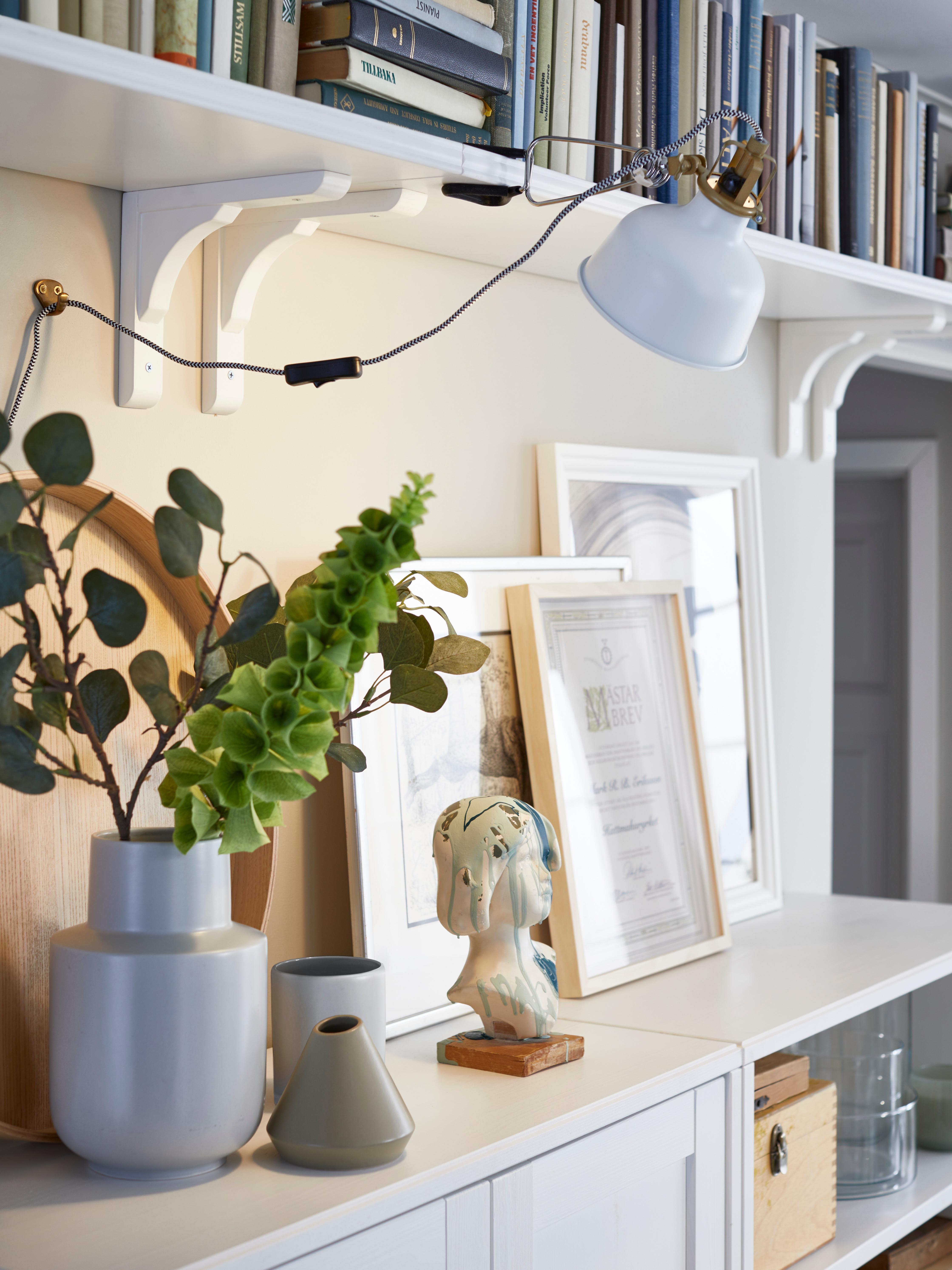 Bele zidne police BERGSHULT postavljene jedna pored druge, čime je dobijena neprekidna polica za knjige u gornjem delu zida, iznad ormarića.