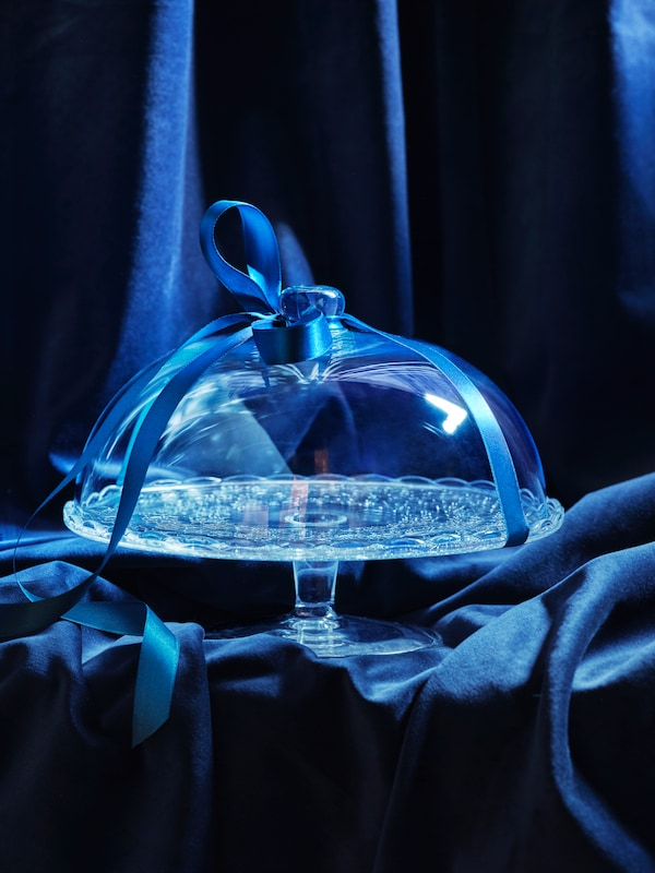 An ARV BRÖLLOP glass cake stand wrapped in a blue ribbon waiting to be gifted.