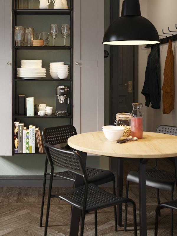 Mesa redonda GAMLARED con cuatro sillas ADDE negras y con una lámpara de techo en negro sobre ella, delante de un módulo de almacenaje con puertas de cristal.