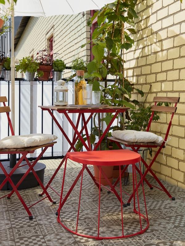 Ein Balkon mit einem TRANARÖ Hocker, einem Tisch und zwei Stühlen mit Kissen. Auf dem Tisch steht eine Laterne.