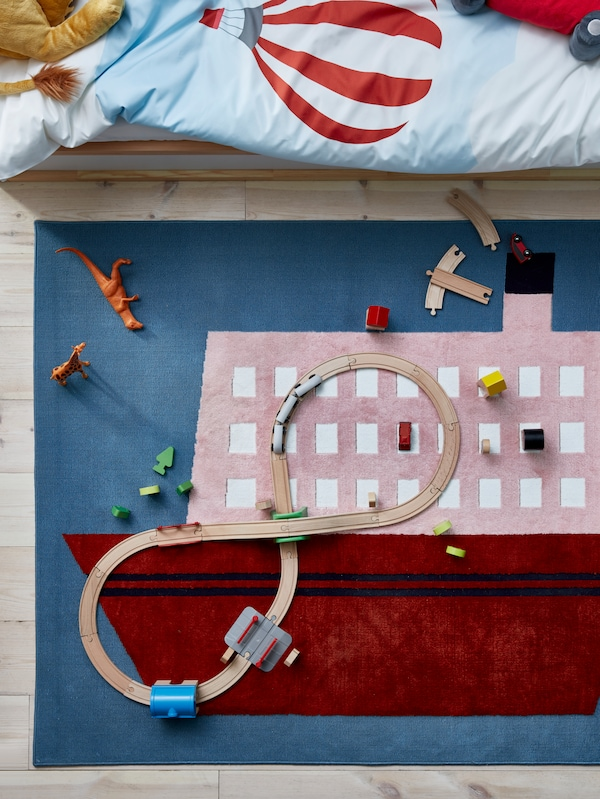 An UPPTÅG rug with a large boat motif lies near a bed. Toys including a wooden train set have been placed on the rug.