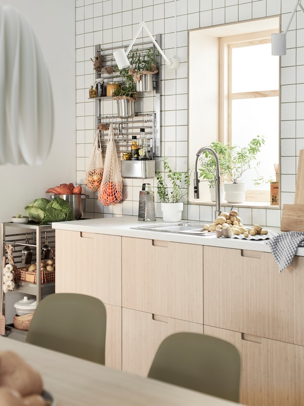A kitchen with FRÖJERED bamboo drawer fronts and two KUNGSFORS wall grids with herbs and jars in containers and net bags.