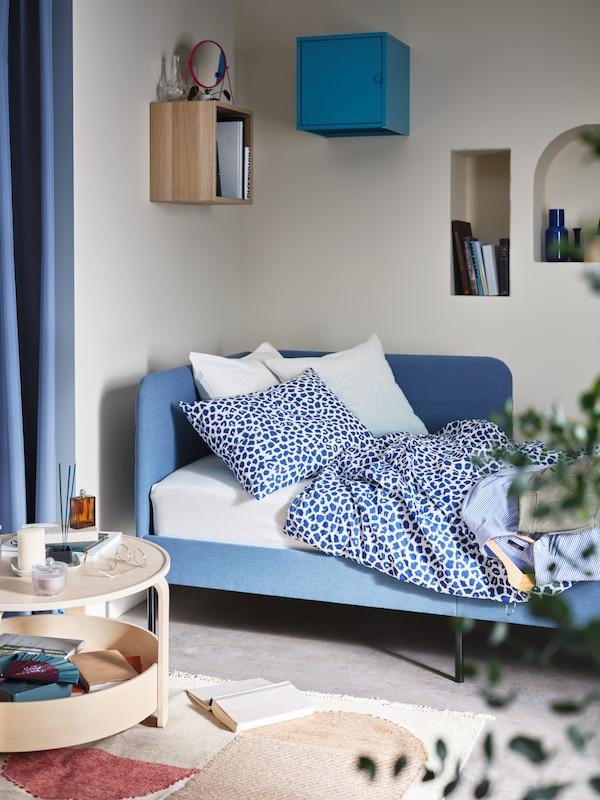 غرفة بهيكل سرير BLÅKULLEN منجّد أزرق متوسط مع لوح رأسي زاوية وطاولة قهوة وزوج من خزائنEKET.