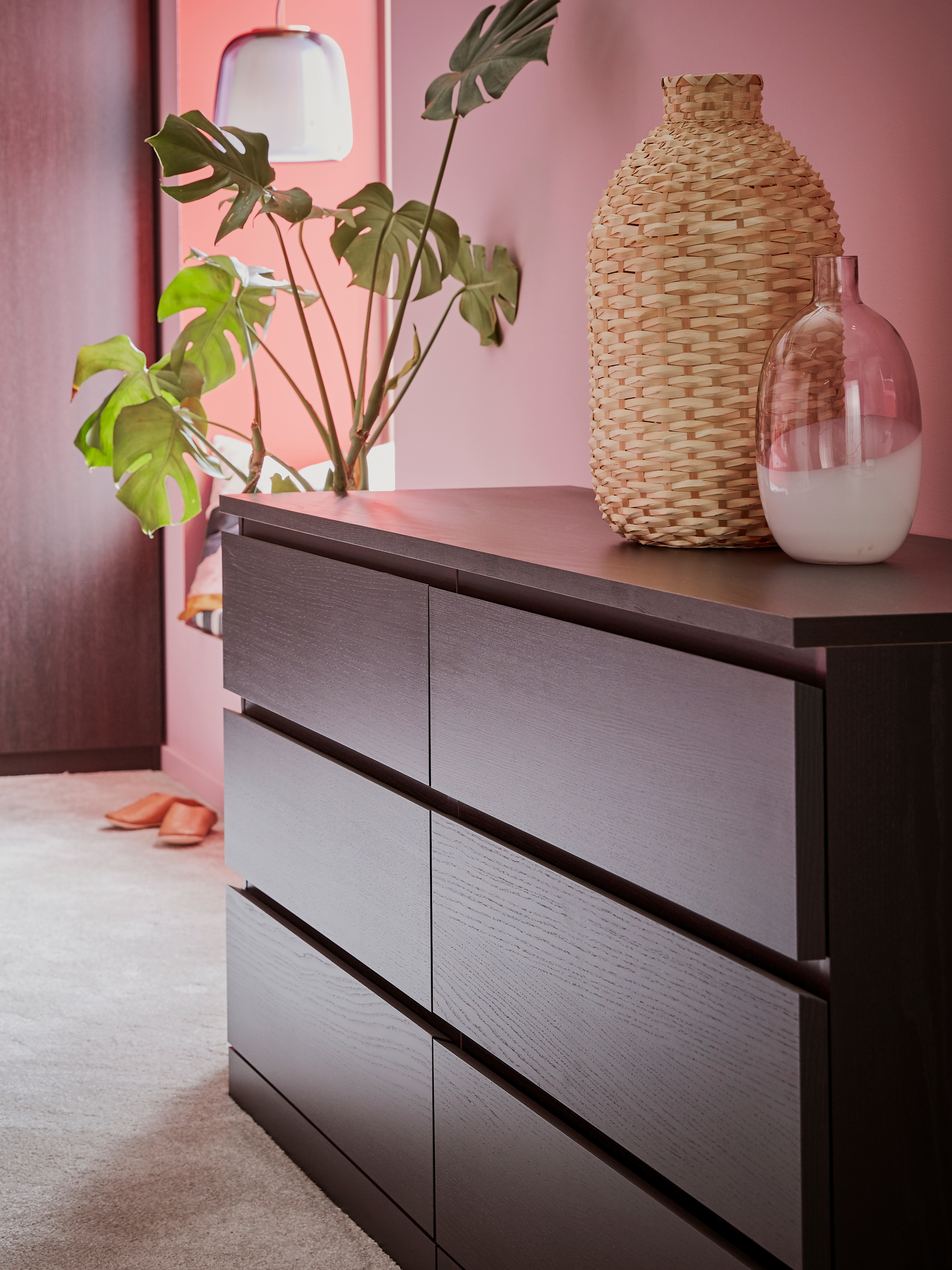 A pink room that has a MALM chest of drawers in a black-brown finish with six drawers and two vases on top.