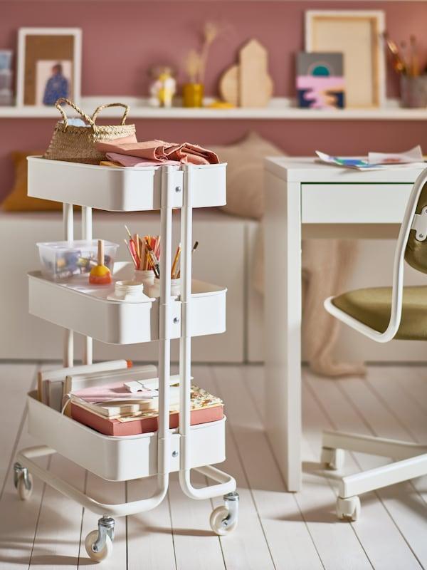 Une desserte RÅSKOG blanche à trois niveaux contenant des crayons, du papier et d'autres articles, située à côté d'un bureau pour enfant et d'une chaise pivotante.