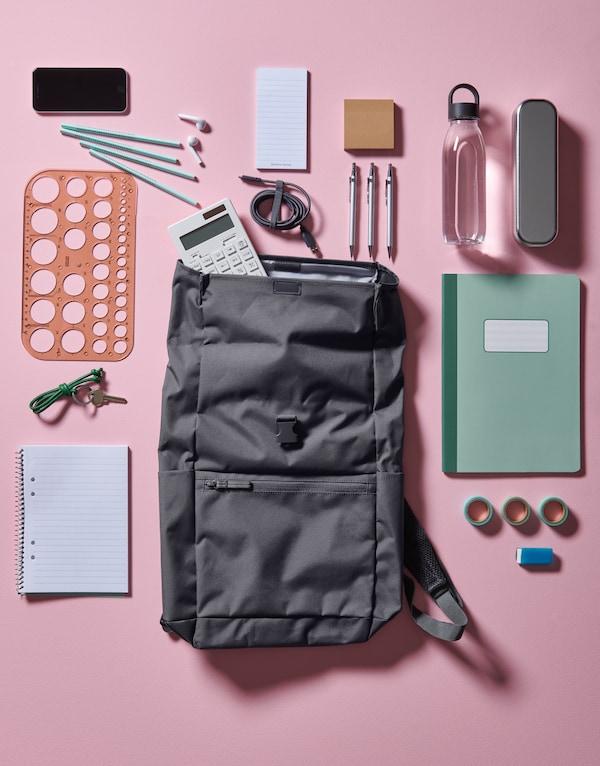 Una mochila con un estampado rosa sobre un suelo rosa, con diferentes materiales escolares a su alrededor, como bolígrafos y clips.