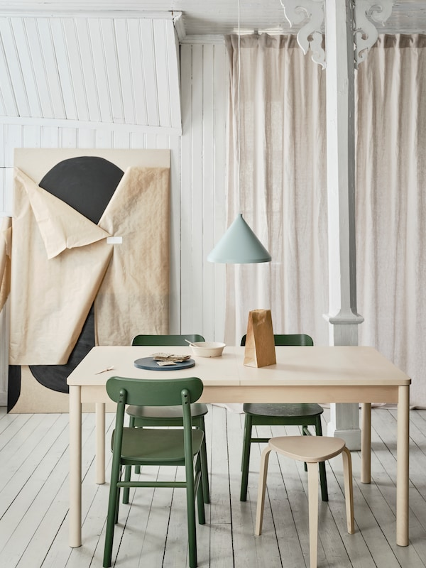 RÖNNINGE extendable table in light birch and rounded legs placed in a dining context with chairs around in a light room.
