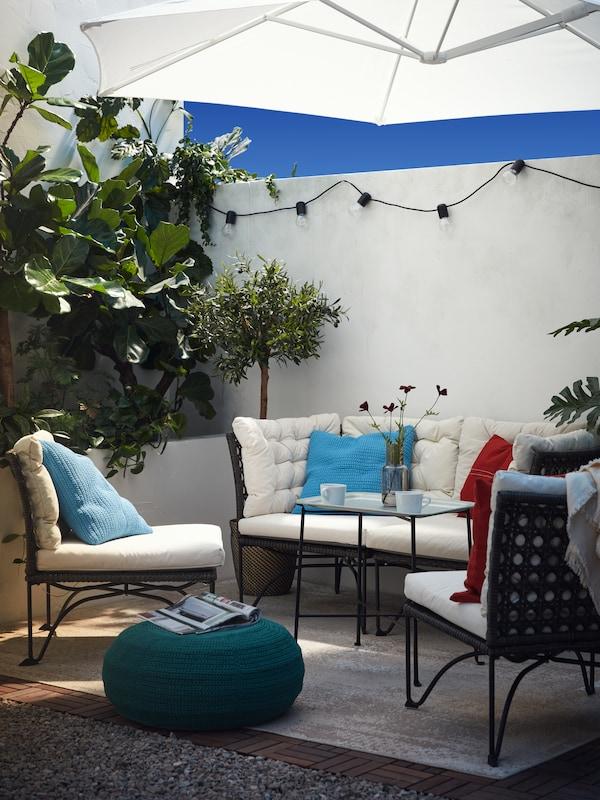 Ein Sitzelement unter einem weissen Sonnenschirm, zwei einzelne Elemente, ein Tabletttisch mit zwei Tassen Kaffee und ein dunkelgrüner Hocker.