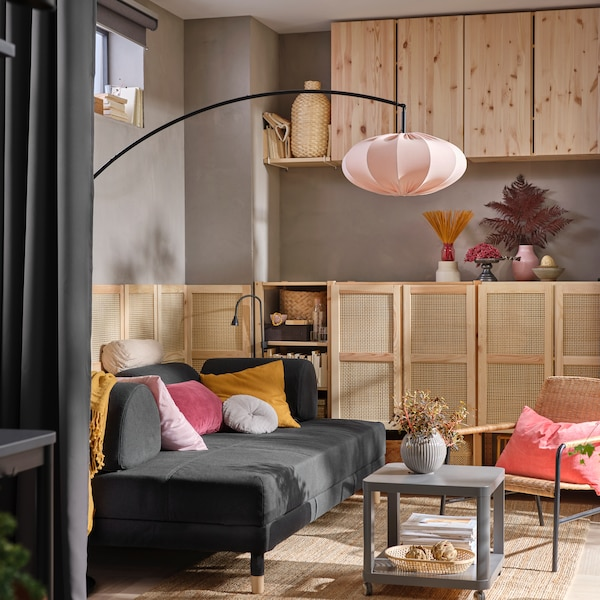 Nástěnné skříňky IVAR v obývacím pokoji s tmavě šedou rozkládací pohovkou FLOTTEBO se žlutými polštáři a odkládacím stolkem TINGBY.