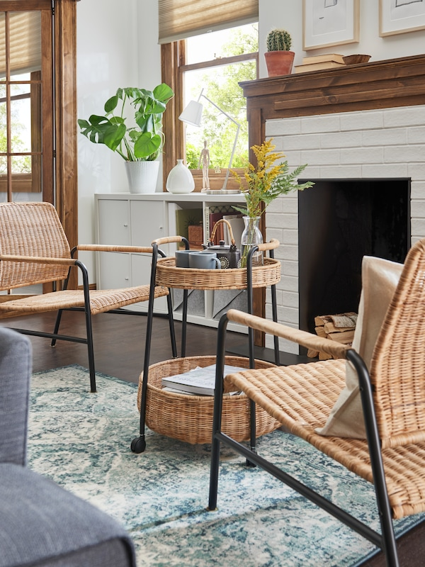 A LUBBAN trolley-table, wicker and steel, between two ULRIKSBERG rattan armchairs, in front of a fireplace.