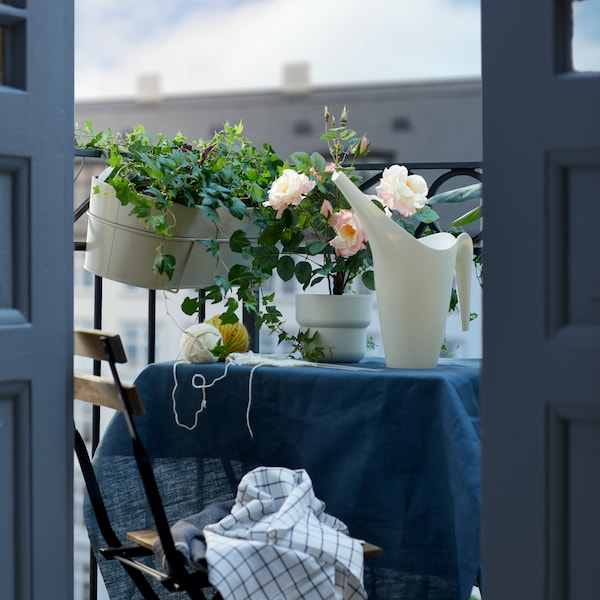 A white flower box hung from a balcony, above a small table with a white watering can.