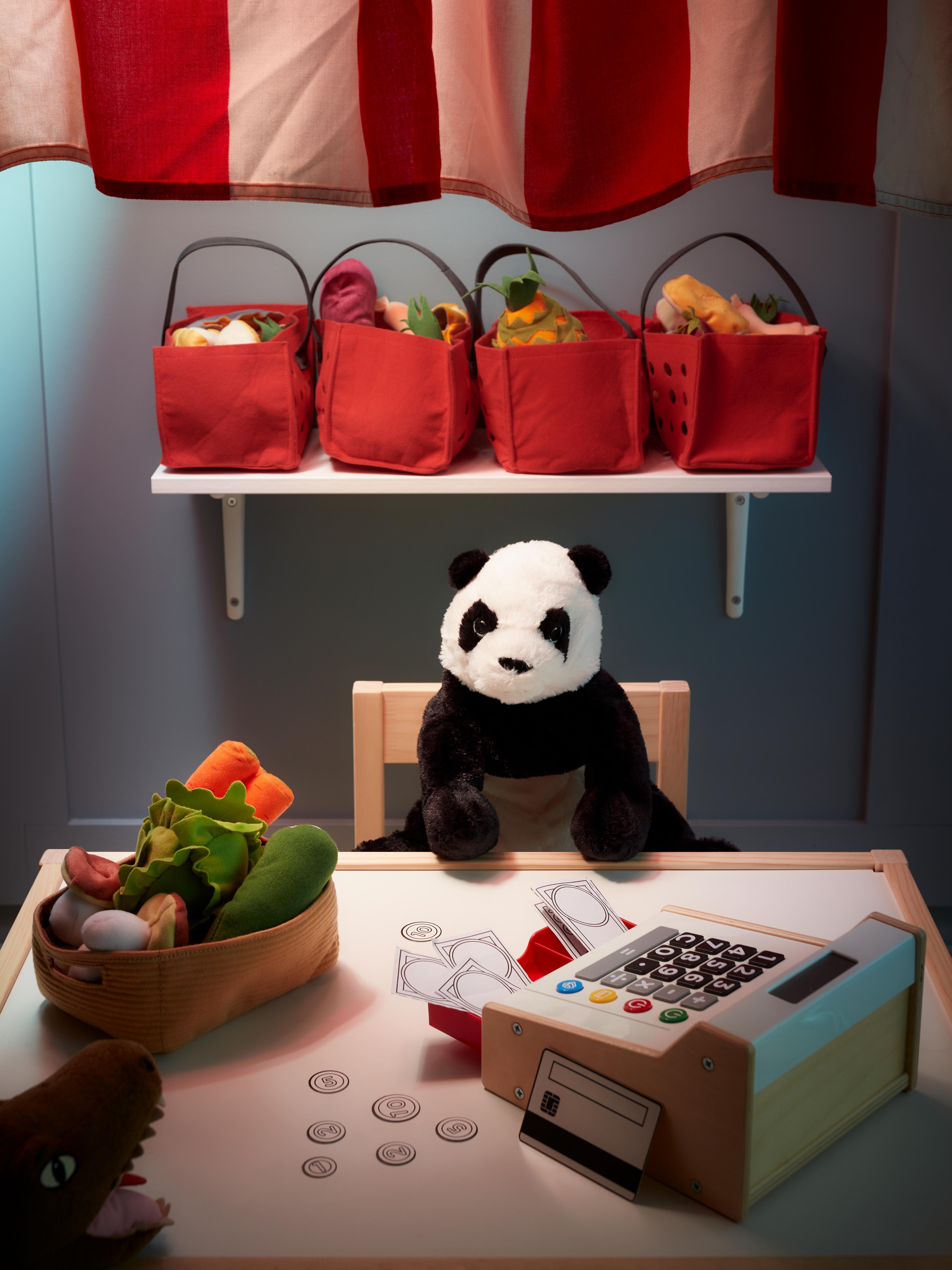 Panda hartza haurraren aulkian eserita. Ondoan duen mahai gainean kutxazaina eta DUKTIG jostailuzko barazki sorta daude.