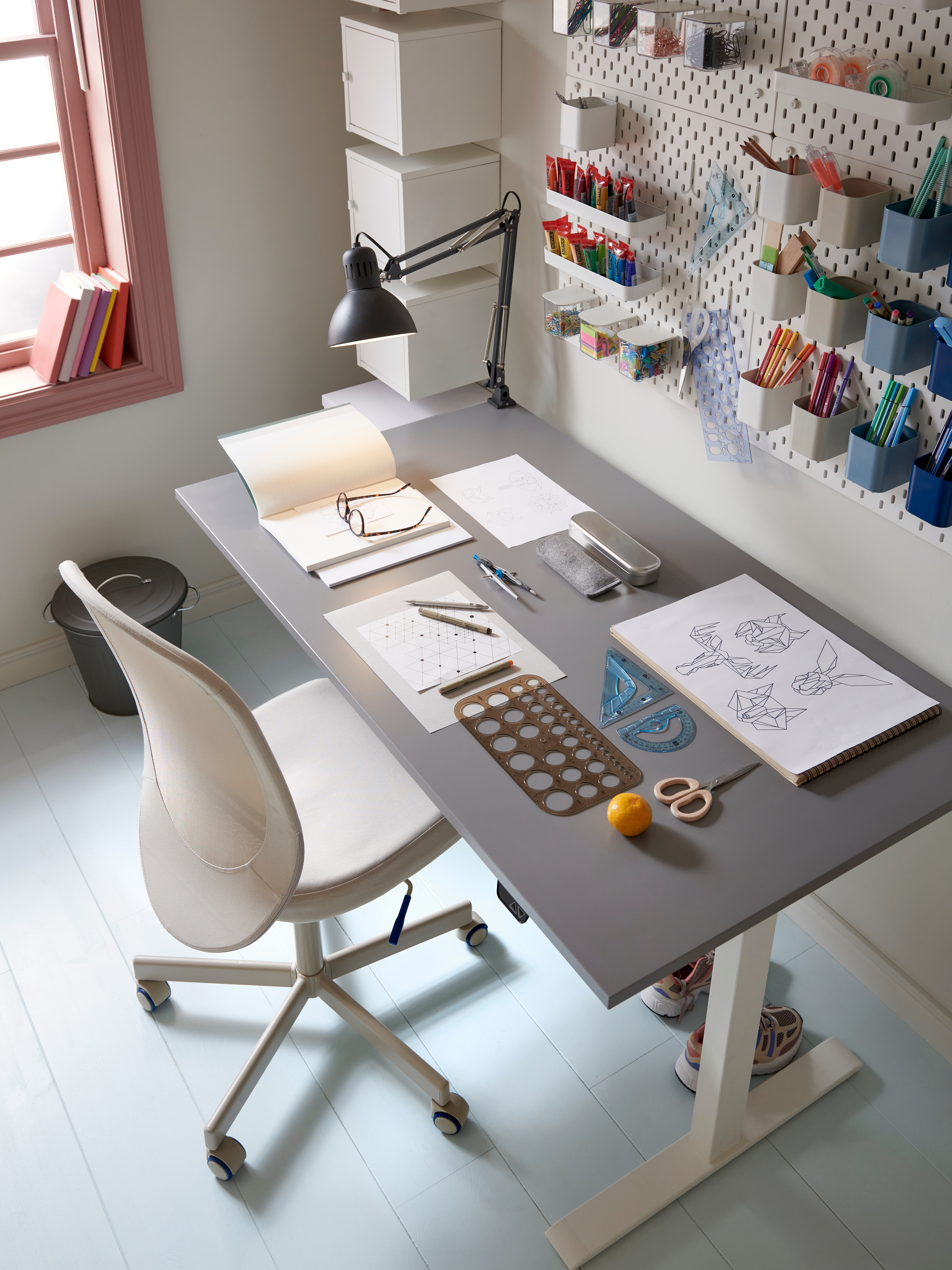 A neat and tidy workspace with a grey desk and white office chair and a pegboard with containers on the wall.