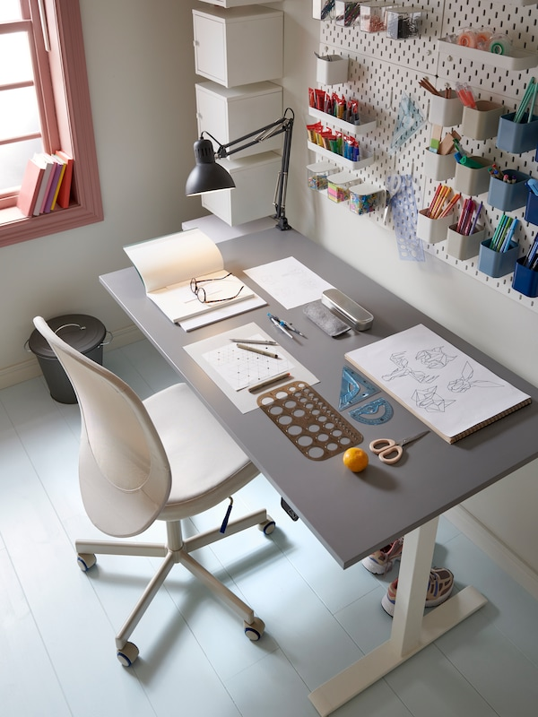 A neat and tidy workspace with a gray desk and beige office chair and pegboards with containers on the wall.