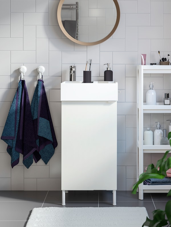 A tiny white bathroom with a white single wash-basin with 1 door, a round mirror above and an open shelving unit beside it.