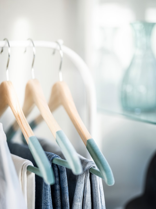 SNYGGING hangers in wood and turquiose on a white clothes rack.