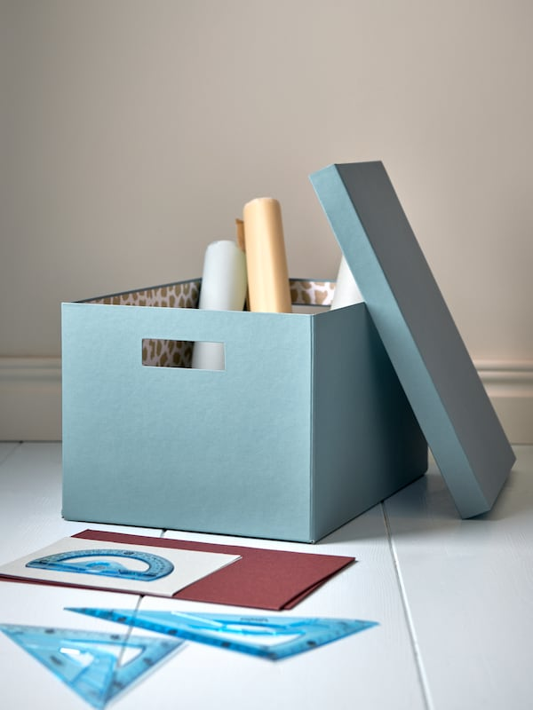 A paper storage box in blue holding rolls of paper, placed on a white floor and its lid leaning against the side of the box.