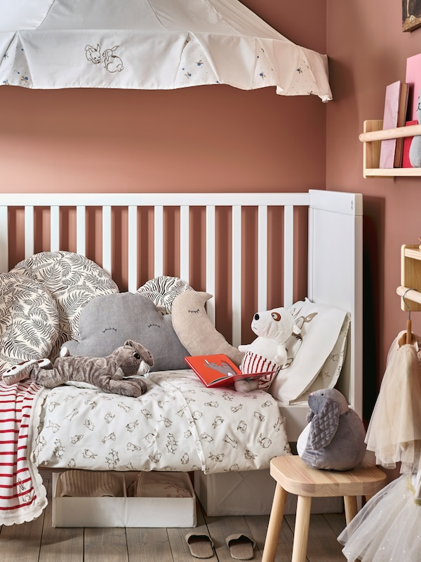 White crib in a pink-walled room with a beige duvet cover and several pillows on top. On top of the crib a white canopy and a wooden bench beside it.