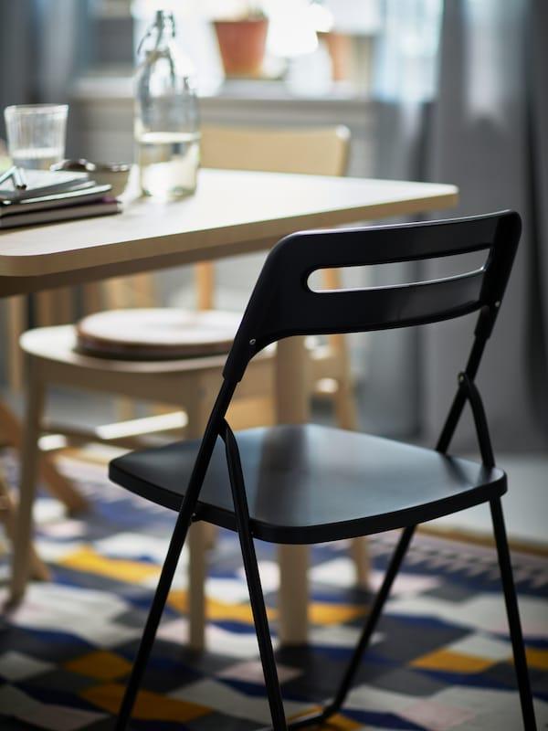 Une chaise pliante NISSE noire à côté d'une chaise RÖNNINGE en bouleau devant une table RÖNNINGE en bouleau, le tout installé sur un tapis TÅRBÄK.