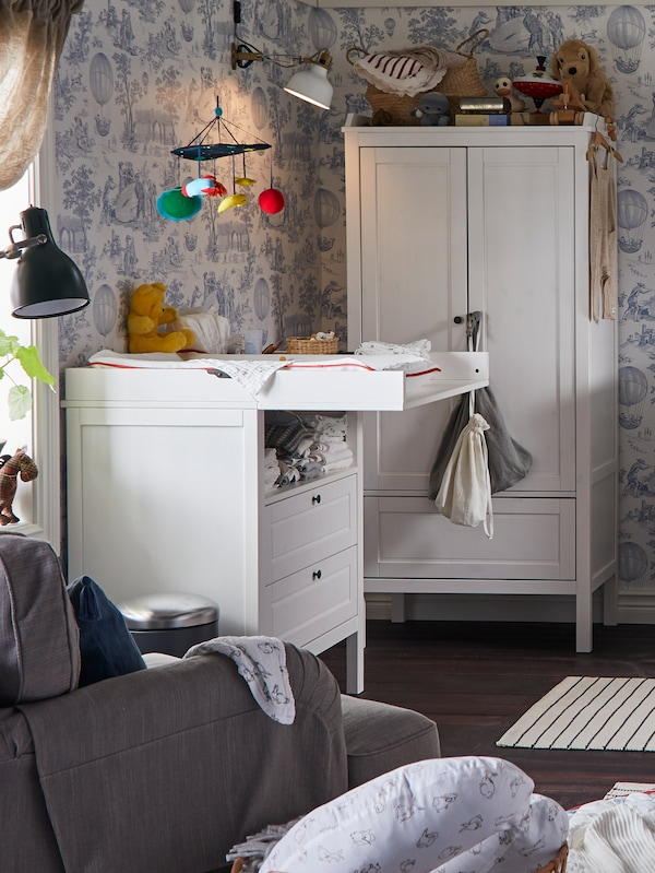 A SUNDVIK changing table stands in a traditional-style children's room next to a window and near a SUNDVIK wardrobe.