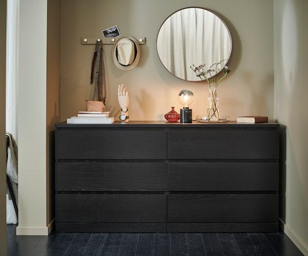 Cassettiera MALM con 6 cassetti, marrone-nero, posizionata contro una parete beige. Sulla cassettiera uno specchio tondo STOCKHOLM, una lampada da tavolo MARKFROST e alcuni oggetti decorativi.