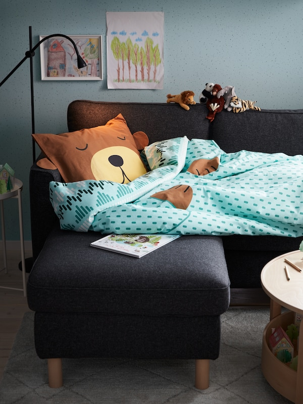 En 3-pers. sofa med chaiselong, en sort LED-gulv-/læselampe, et turkis sengesæt designet som en sovende bjørn og en bog.